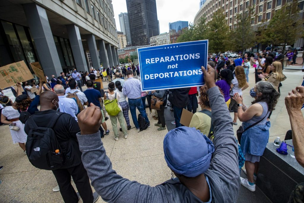 About 200 people gathered for the Solidarity with Haiti demonstration at John F. Kennedy Federal Building in Downtown Boston to protest the inhumane treatment of Haitian immigrants at the Texas border. (Jesse Costa/WBUR)